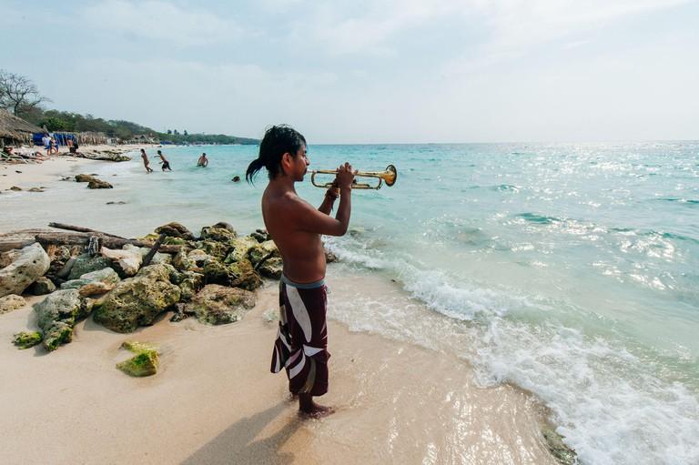 Colombia, cartagena - junio de 2019 Ver en la playa paradisíaca de Playa Blanca con saxofonista en la isla Barú de Cartagena