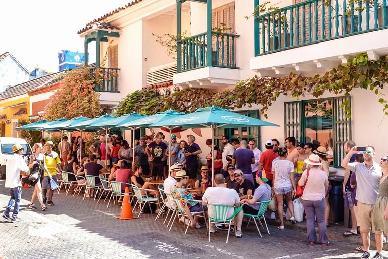 Cartagena Colombia ciudad amurallada vieja centro Centro La Cevicheria restaurante popular mesas al aire libre sombrillas abarrotado hombre mujer ocupada